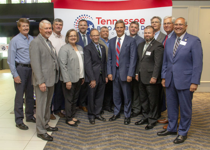 Governor Bill Lee, Levoy Knowles, and others standing in front of a Tennessee Broadband Association banner at a conference
