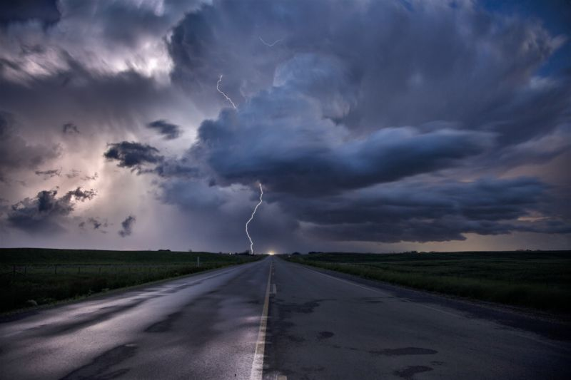 storm clouds over a road and fields with lightning striking in the distance