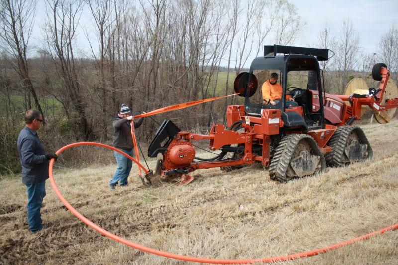 a crew installing fiber line underground in a rural area