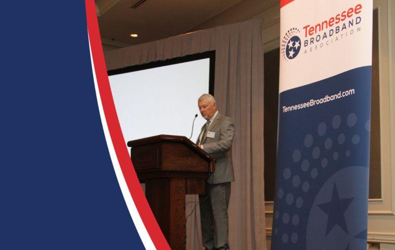 man speaking at podium at convention