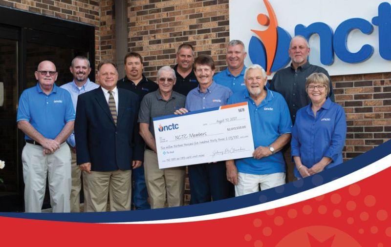 NCTC staff holding large check of capital credits to members