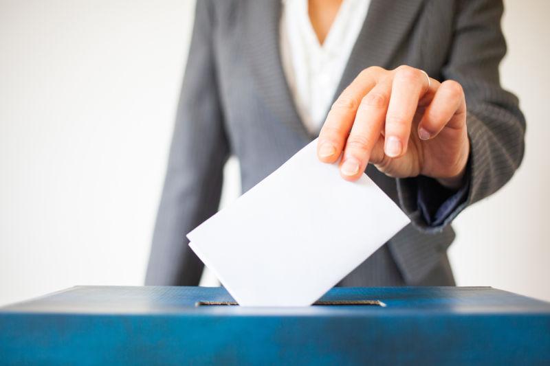 woman dropping ballot in box
